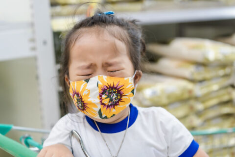 young girl upset while wearing mask