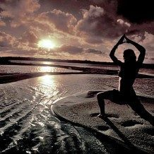 person doing yoga on the beach at sunrise