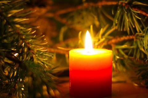 A lit candle surrounded by a fir tree branch