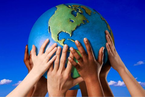 Lots of different hands holding up a globe of Earth