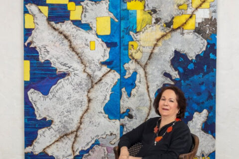 Mira Lehr posing in front of blue, yellow, and grey artwork