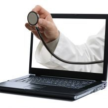 doctor's hand holding stethoscope coming out of computer screen representing telemedicine