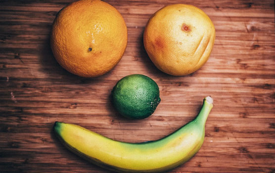 Oranges, lime, and banana in the shape of a smile