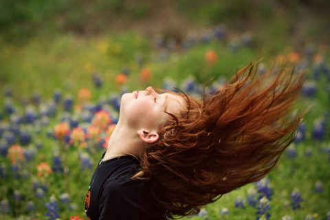 Girl with Red Hair Flipping Her Hair over Head With Her Eyes Closed in a Field of Flowers