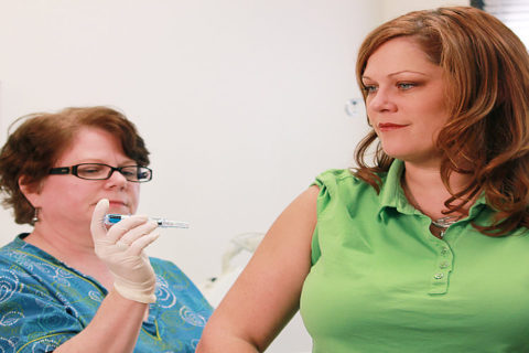 Woman giving another woman a flu shot in her upper right arm