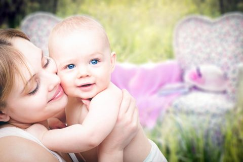 mother with light brown hair holding her blue eyed baby in front of some grass and a white, purple, and pink chair